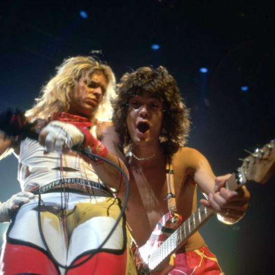 "DETROIT - JULY 3: Dutch-American musician, songwriter and lead guitarist of the hard rock band Van Halen, Eddie Van Halen, and American rock vocalist, musician, songwriter and original lead singer of Van Halen, David Lee Roth, perform during the band's ""Fair Warning Tour"" on July 3, 1981, at Cobo Arena in Detroit, Michigan. (Photo by Ross Marino/Getty Images)"