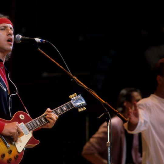 LONDON, UNITED KINGDOM - JULY 13: Singers Sting (R) and Mark Knopfler from rock band Dire Straits (L) perform at the Live Aid concert at Wembley Stadium in London, 13th July 1985. The concert raised funds for famine relief in Ethiopia. (Photo by Georges De Keerle/Getty Images)