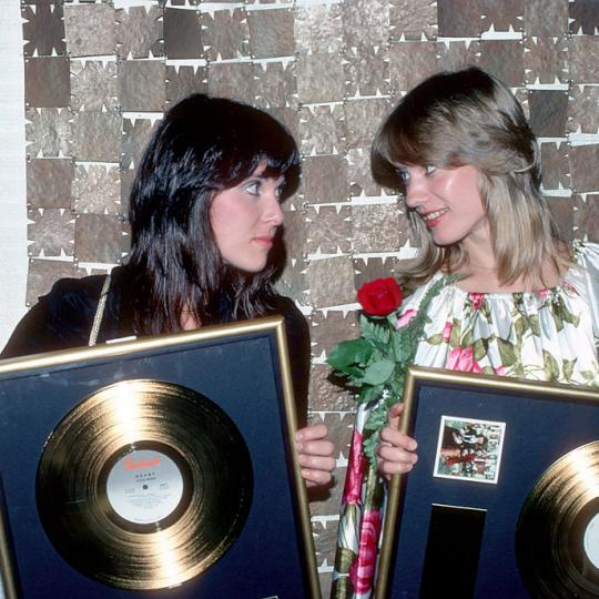 "MAY 1977: Ann Wilson and Nancy Wilson of the rock and roll band ""Heart"" pose for a portrait holding gold records they were awarded by the RIAA for a milestone in sales of their second album ""Little Queen"" which was released in May 1977. (Photo by Michael Ochs Archives/Getty Images)"